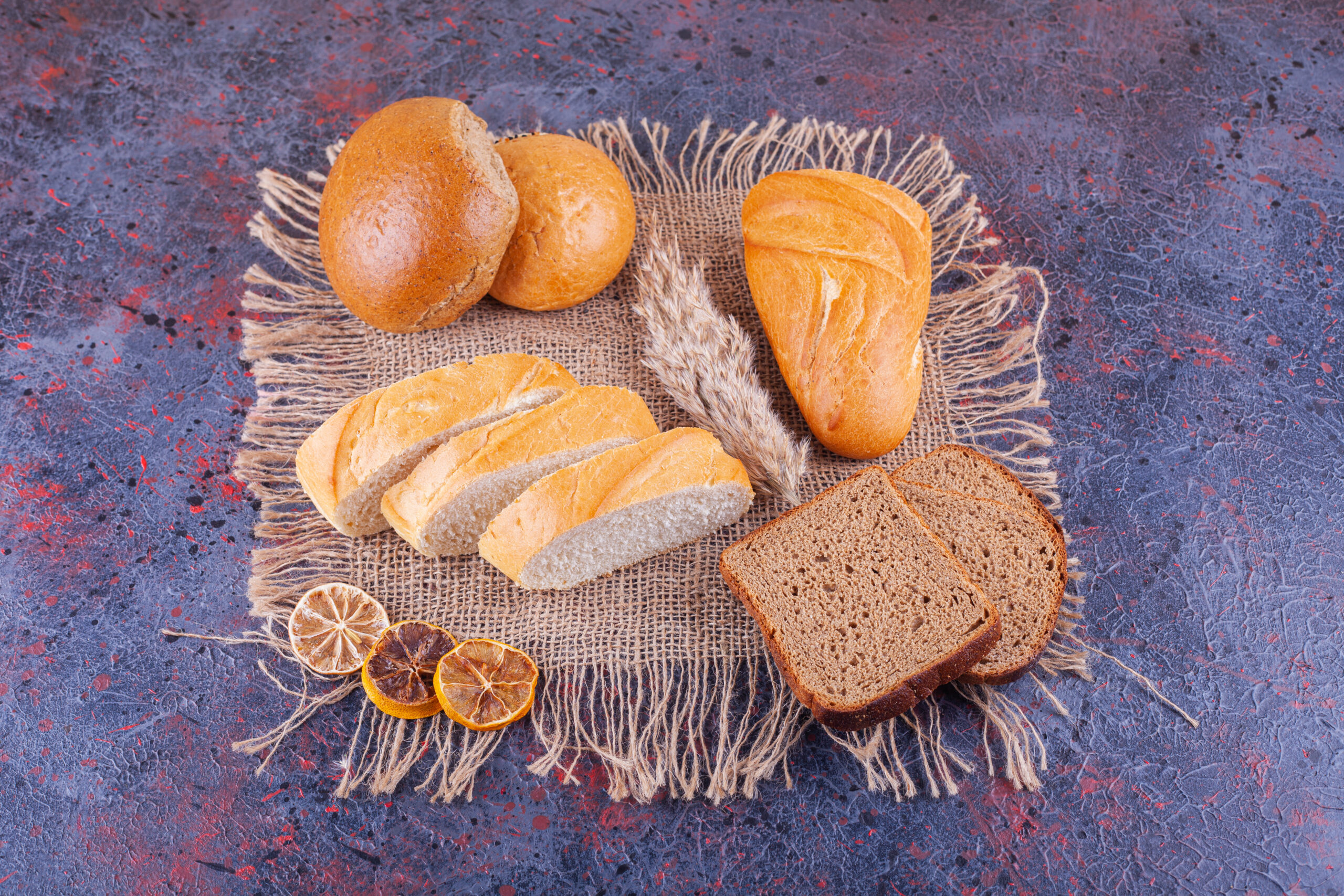 pile of various sliced fresh bread on blue background